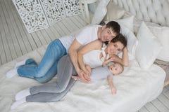 HOOGSTE MENING: De jonge gelukkige familie ligt op een bed met hun kleine zuigeling royalty-vrije stock fotografie