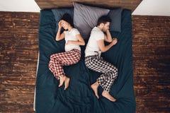 Hoogste mening De jonge zwangere vrouw ervaart samentrekkingen, die naast de slaap volwassen mens liggen stock fotografie