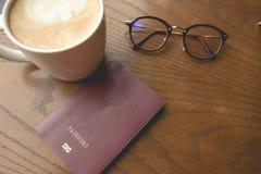 Hoogste mening de kop met koffie naast paspoort wordt geplaatst dat en heeft glasse Royalty-vrije Stock Afbeeldingen