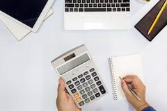 Hoogste mening De mens gebruikend calculator en schrijvend maakt nota stock afbeeldingen