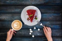 Hoogste mening De plak van heerlijke Rode fluweelcake en latte koffie met vrouwen` s handen en rafinated suiker op gekleurde hout Royalty-vrije Stock Fotografie