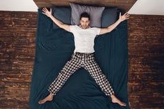 Hoogste mening De volwassen vrolijke mens toont ster, plaatsend armen en benen opzij op bed stock foto's