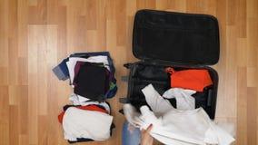 Hoogste mening die van aantrekkelijke vrouw zich op houten vloer en uitpakkende kleren van een koffer bevinden stock video