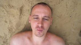 Hoogste mening die van de jonge mens bellen opblazen die op het strand liggen stock videobeelden