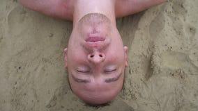 Hoogste mening die van de jonge mens bellen opblazen die op het strand liggen stock video