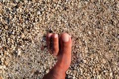 Hoogste mening die van de mens naakte voeten op strand bevindt zich Textuur van bodem, been en voet van de mens die met het vegen royalty-vrije stock afbeelding