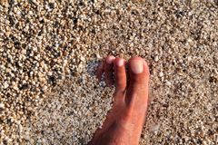 Hoogste mening die van de mens naakte voeten op strand bevindt zich Textuur van bodem, been en voet van de mens die met het vegen royalty-vrije stock foto's