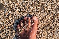 Hoogste mening die van de mens naakte voeten op strand bevindt zich Textuur van bodem, been en voet van de mens die met hieronder royalty-vrije stock foto's