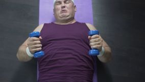 Hoogste mening die van de te zware mens op de vloer en de opheffende domoren met inspanning liggen stock video
