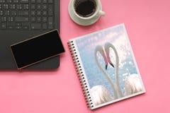 Hoogste mening die van flamingo's tot een hartvorm in maken boeken met smartphone op laptop computer en kop van koffie op roze ac stock afbeelding