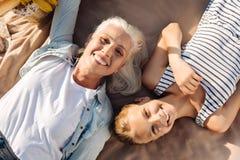 Hoogste mening die van glimlachende vrouw en haar kleindochter in het park liggen Royalty-vrije Stock Foto's