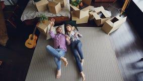 Hoogste mening die van het houden van van paar op slaapkamervloer in nieuwe flat liggen en het spreken Gitaar, ingepakte dingen i stock videobeelden