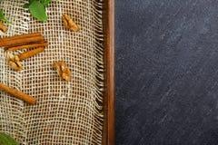 Hoogste mening die van kaneel met okkernoten en groene bladeren op een wit servet op een houten dienblad op een donkere steenacht Royalty-vrije Stock Afbeeldingen