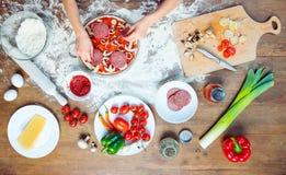 Hoogste mening die van kind pizza met pizzaingrediënten, tomaten, salami en paddestoelen maken Stock Afbeeldingen