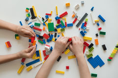 Hoogste mening die van kinderen` s handen met kleurrijke plastic bakstenen spelen stock foto