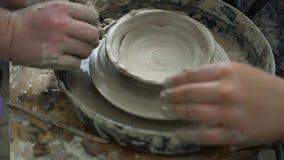 Hoogste mening die van leerling een ceramische kom met hulp van leraar op aardewerkwiel maken in een workshop stock video