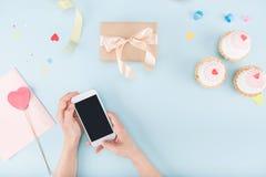 Hoogste mening die van menselijke handen smartphone met cakes en het model van de giftdoos houden Stock Afbeelding