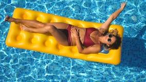 Hoogste mening die van mooi gelooid meisje in zonnebril en rode bikini op gele opblaasbare matras in zwembad liggen