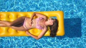 Hoogste mening die van mooi gelooid meisje in zonnebril en roze bikini op gele opblaasbare matras in zwembad liggen stock footage
