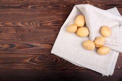 Hoogste mening die van nieuwe tedere aardappels op een wit servet, nieuwe aardappels op een houten lijst aangaande een donkere br Stock Afbeeldingen