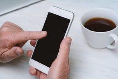 Hoogste mening die van oude mensenhand een kop van koffie en smartphone houden stock afbeeldingen