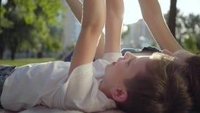 Hoogste mening die van oudere zuster met jongere broer op de deken in openlucht liggen De jongen en het meisje die samen in het p stock videobeelden