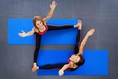 Hoogste mening die van twee vrouwen zich tijdens de klassen van de pilatesgeschiktheid uitrekken Royalty-vrije Stock Foto's