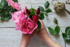 Hoogste mening die van vrouwelijke decorateur rozen op de houten lijst schikken royalty-vrije stock foto