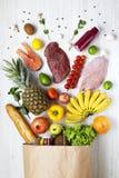 Hoogste mening, document zak van natuurlijke voeding op een witte houten achtergrond Van hierboven, vlak leg Royalty-vrije Stock Afbeelding