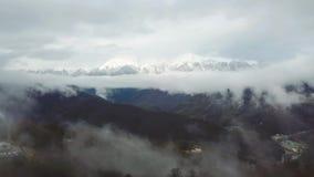 Hoogste mening door wolken op sneeuwpieken van bergvallei Mooi landschap van bergpieken die zijn manier door maken stock footage