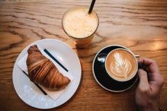 Hoogste mening Een mens neemt een kop van hete geurige cappuccino Dichtbij de lijst is een croissant en een glas met verse sinaas royalty-vrije stock fotografie