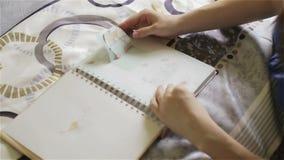 Hoogste mening Een zwangere vrouw met een grote buik met een fotoalbum in haar handen stock footage