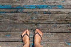Hoogste mening, foto van vrouwelijke benen in strandwipschakelaars op een houten oude vloer Foto's op vakantie, strand, de zomer royalty-vrije stock fotografie
