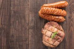 Hoogste mening geroosterde lapje vlees en worst op een houten achtergrond royalty-vrije stock fotografie