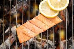 Hoogste mening geroosterde zalm met citroen op de vlammende grill stock foto's