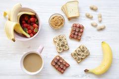 Hoogste mening, gezond ontbijt: latte, veganisttoosts met vruchten, zaden, pindakaas Witte Houten Achtergrond Van hierboven stock foto