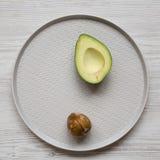 Hoogste mening, halve avocado met been op een plaat over witte houten achtergrond Lucht, van hierboven, vlak leg royalty-vrije stock foto