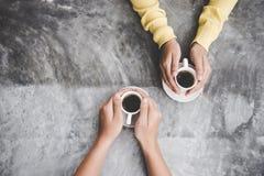 Hoogste mening met exemplaarruimte Paar in de handen van de liefdeholding met koffieliefde op lijst, uitstekende toon Stock Foto