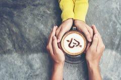 Hoogste mening met exemplaarruimte Paar in de handen van de liefdeholding met koffieliefde op lijst, uitstekende toon royalty-vrije stock foto