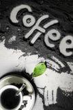 Hoogste mening over kop van hete zwarte koffie met de groene die bladeren en hand van het tekstwoord in Engelse `-koffie ` in gem Stock Foto's