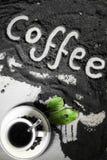 Hoogste mening over kop van hete zwarte koffie met de groene die bladeren en hand van het tekstwoord in Engelse `-koffie ` in gem Royalty-vrije Stock Fotografie