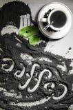 Hoogste mening over kop van hete zwarte koffie met de groene die bladeren en hand van het tekstwoord in Engelse `-koffie ` in gem Stock Afbeeldingen
