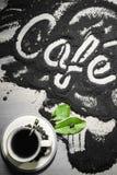 Hoogste mening over kop van hete zwarte koffie met de groene die bladeren en hand van het tekstwoord in Franse ` café ` in gemal Stock Foto's