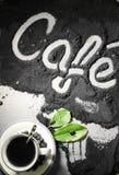 Hoogste mening over kop van hete zwarte koffie met de groene die bladeren en hand van het tekstwoord in Franse ` café ` in gemal Stock Afbeeldingen