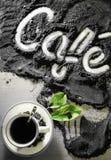 Hoogste mening over kop van hete zwarte koffie met de groene die bladeren en hand van het tekstwoord in Franse ` café ` in gemal Royalty-vrije Stock Fotografie