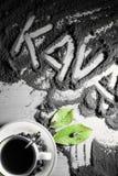 Hoogste mening over kop van hete zwarte koffie met de groene die bladeren en hand van het tekstwoord in Sloveense taal` kava ` wo Stock Afbeeldingen