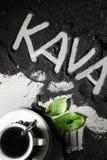 Hoogste mening over kop van hete zwarte koffie met de groene die bladeren en hand van het tekstwoord in Sloveense taal` kava ` wo Stock Fotografie