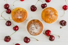 Hoogste mening over muffins met kersen op wit houten bureau Stock Afbeeldingen