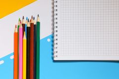 Hoogste mening over notitieboekjes, kleurpotloden, op een blauwe achtergrond Terug naar het Concept van de School royalty-vrije stock foto's