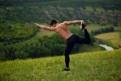 Hoogste mening over steen, atleten jonge mens met naakt torso in sportkleding die uitrekkende oefeningen, landschapsachtergrond d stock afbeeldingen